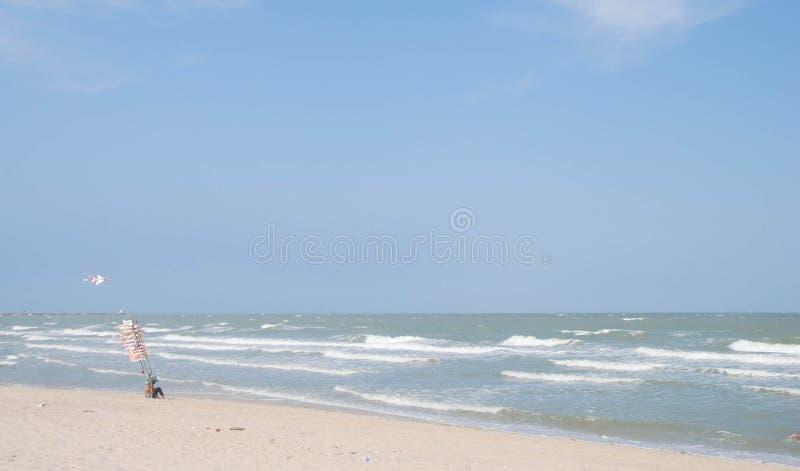 Bilda sammanträde för flygplanleksaksäljaren på sanden på stranden fotografering för bildbyråer