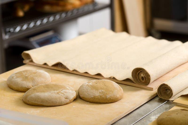 Bildade loaves på degbräde royaltyfria foton