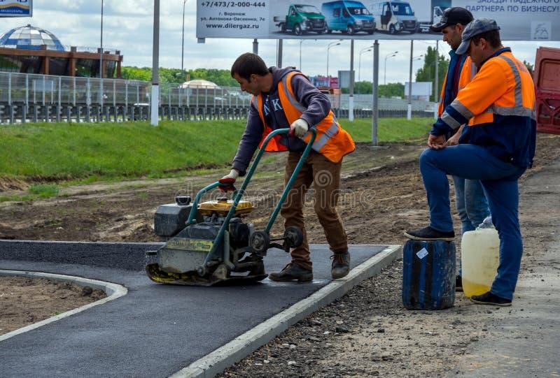 Bildande av ett asfaltlager på trottoaren genom att använda en vibreringsmaskin royaltyfri foto