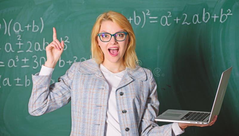 Bildande plats f?r l?rare Smart klyftig dam f?r utbildare med den moderna b?rbara datorn som s?ker svart tavlabakgrund f?r inform arkivbild