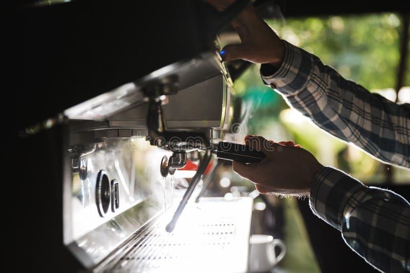 Bildcloseup av den caucasian baristamannen som gör kaffe, medan arbeta i det utomhus- kafét eller kafét arkivbilder