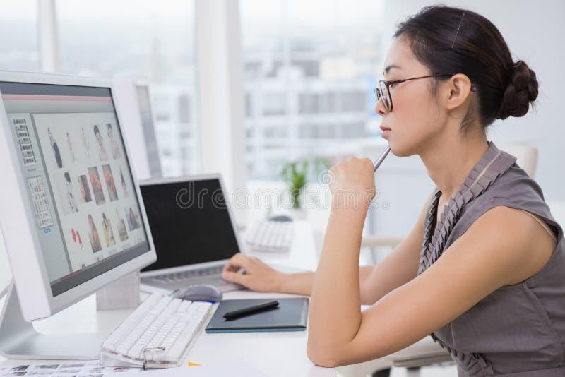 Bildeditor, der an ihrem Schreibtisch arbeitet stockbilder
