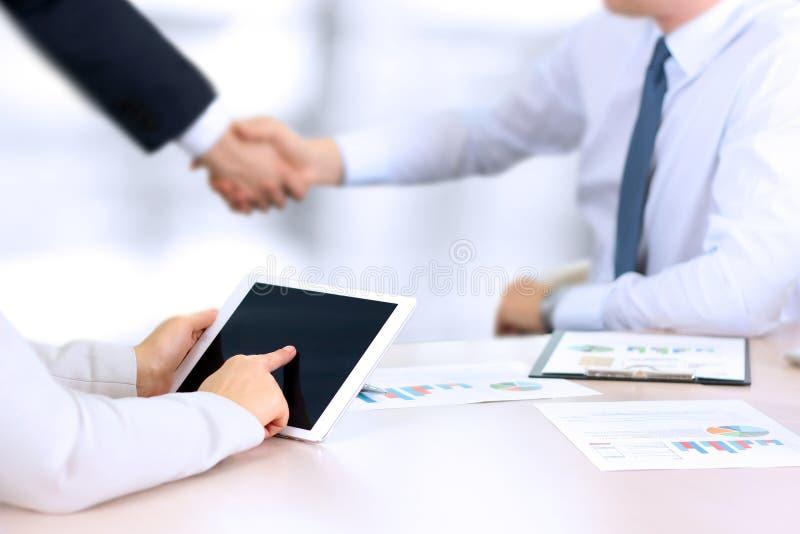 Bilden av affärspartnerhandshaking över affär anmärker på arbetsplats Affärskvinna som fungerar med den digitala tableten arkivbilder