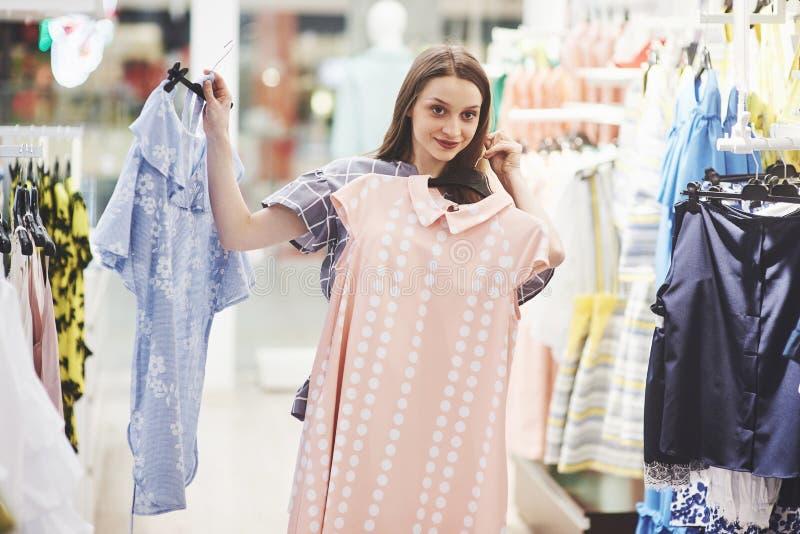 Bilden av anseendet för den unga damen i kläder shoppar välja inomhus klänningar åt sidan se royaltyfri bild