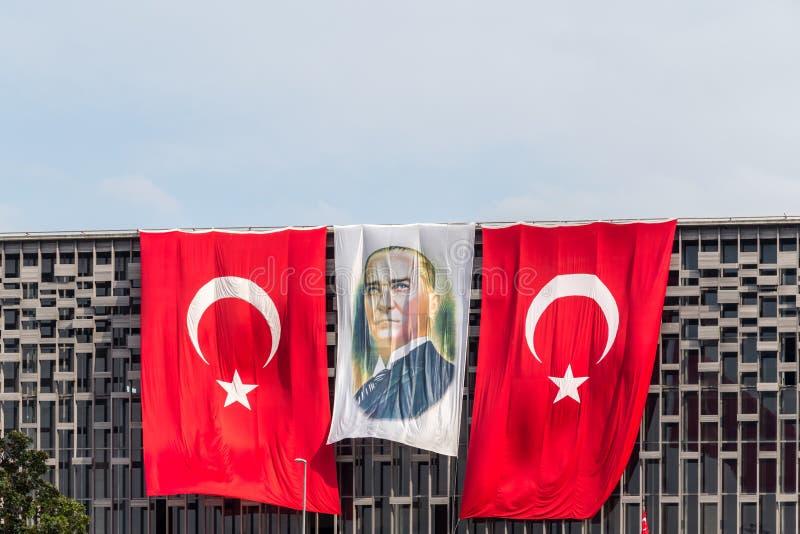 Bilden av Ataturk står mellan turkiska flaggor arkivbild