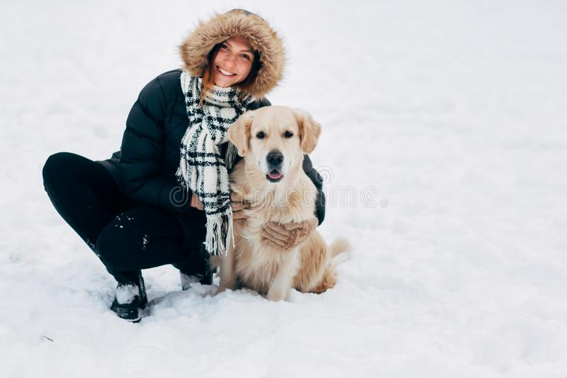 Bilden av att le kvinnan med labrador i vinter parkerar arkivbild
