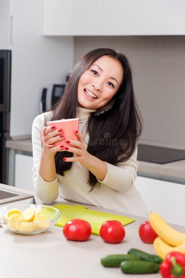 Bilden av att le kvinnan med rånar i händer som står på tabellen med grönsaker och frukter arkivfoto