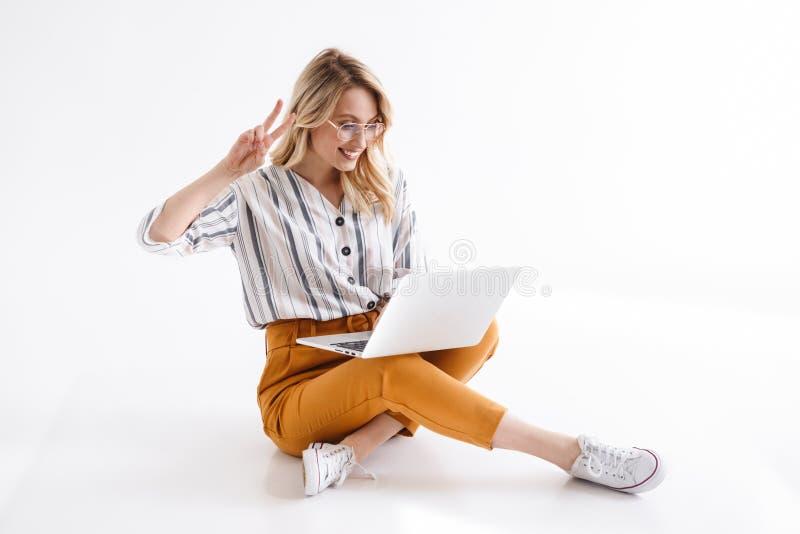 Bilden av b?rande exponeringsglas f?r den blonda kvinnan genom att anv?nda b?rbara datorn och visa fred sjunger, medan sitta p? g arkivfoton