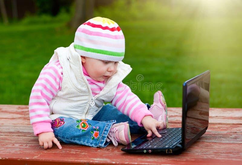 Bilden av behandla som ett barn att spela med bärbar datordatoren royaltyfri fotografi
