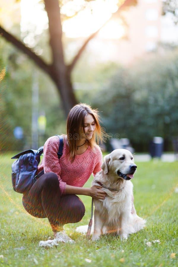 Bilden av brunetten med ryggsäcken går på med apportörn fotografering för bildbyråer