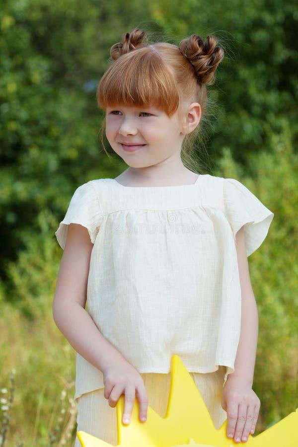 Bilden av den älskvärda rödhåriga flickan som in poserar, parkerar royaltyfria bilder