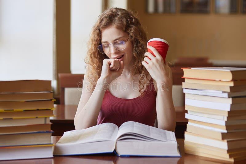 Bilden av den attraktiva seepy studenten som sitter i läsningrum och gäspar som förbereder sig för grupper, arbetsövertid, blicka arkivbilder