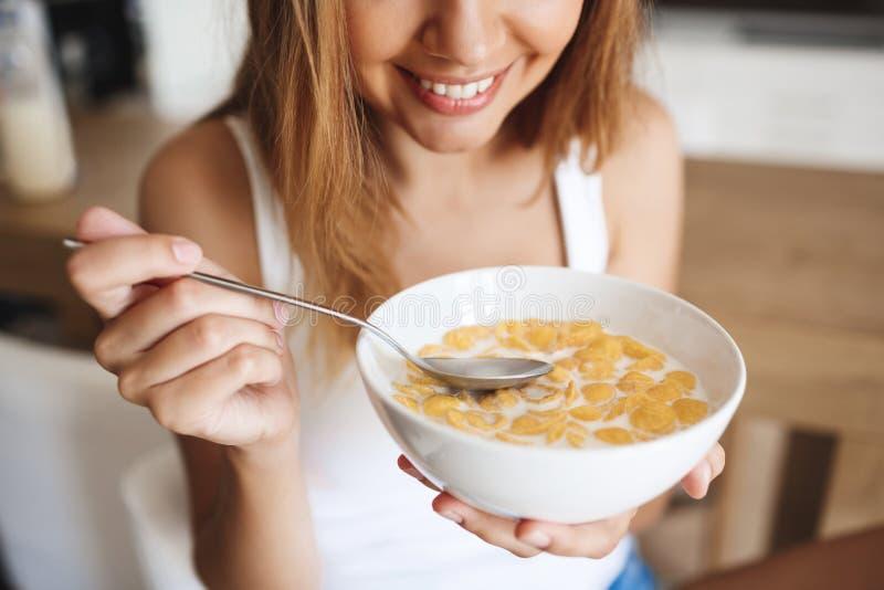 Bilden av den attraktiva unga flickan som äter cornflakes med, mjölkar på kök royaltyfria bilder