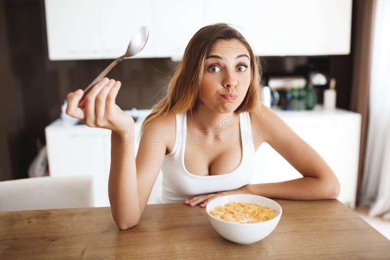 Bilden av den attraktiva unga flickan som äter cornflakes med, mjölkar på kök och framställningsgyckel arkivbilder