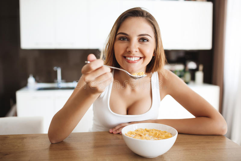 Bilden av den attraktiva unga flickan som äter cornflakes med, mjölkar på köklookig på att le för kamera arkivfoton