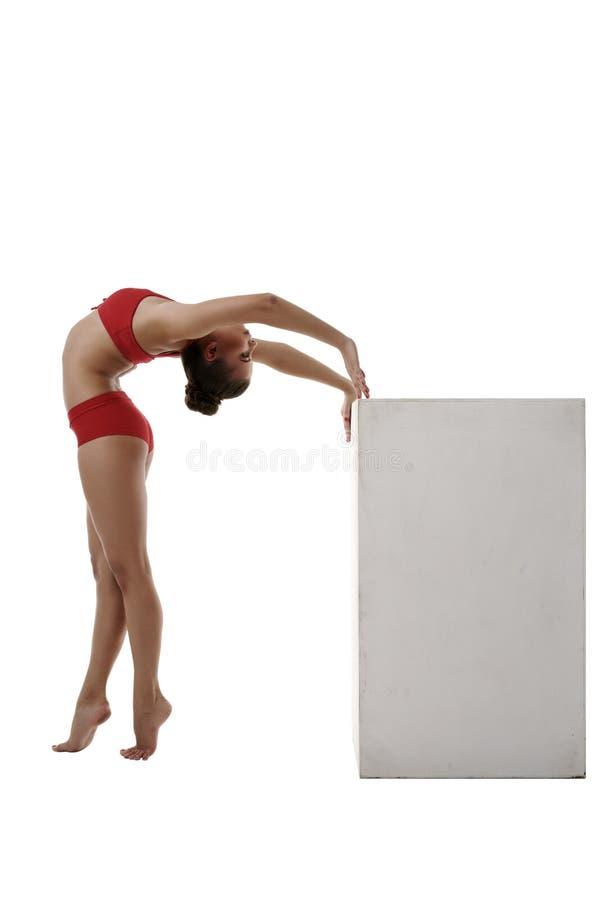 Bilden av den böjliga gymnasten välva sig henne tillbaka för att skära i tärningar arkivbild