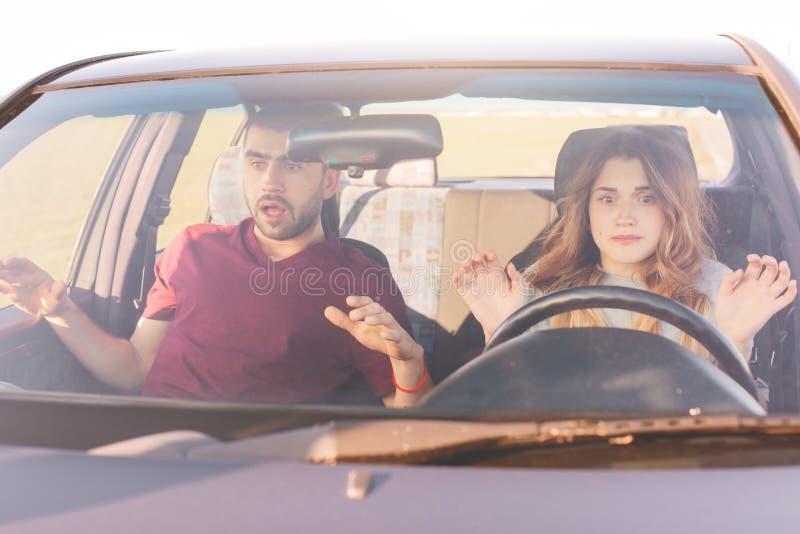 Bilden av den härliga kvinnan på hjulet lär att köra, hennes make sitter på framsätet, unga den skrämde familjblicken, har någon  arkivfoton