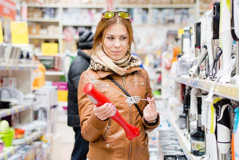 Bilden av den härliga unga kvinnan i en supermarket väljer anordningståenden arkivfoto