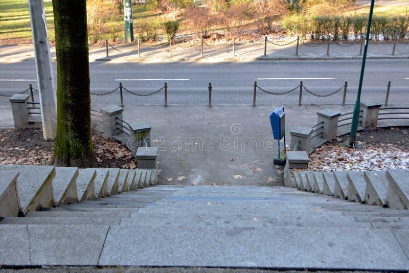 Bilden av den konkreta stenen kliver trappan som ner går till gatan med sikt av, parkerar i bakgrund arkivfoton
