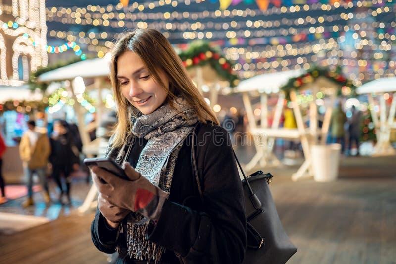 Bilden av den lyckliga flickan med exponeringsglas och telefonen i händer i aftonen för går royaltyfri fotografi