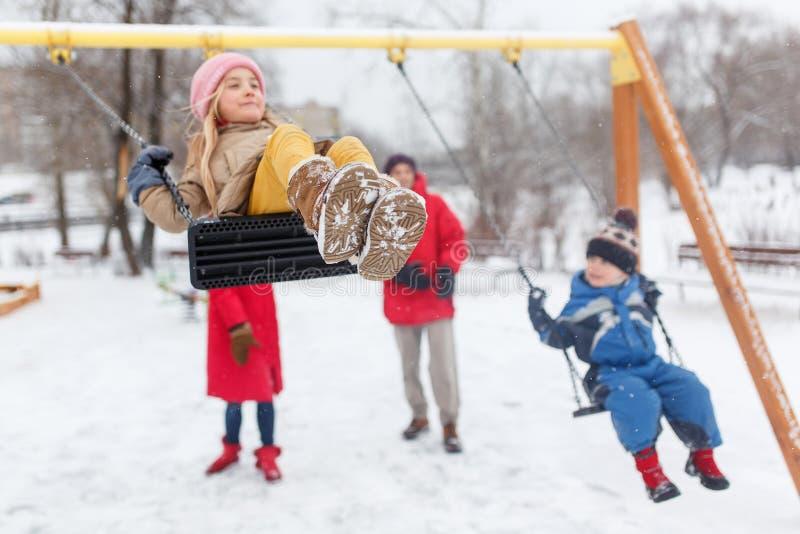 Bilden av den lyckliga flickan och pojken som svänger i vinter parkerar in, med föräldrar royaltyfria foton