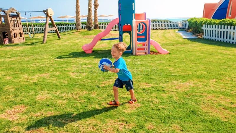 Bilden av den lyckliga skratta gladlynta pojken som rymmer fotbollbollen i h?nder och spring p? barnlekplats p?, parkerar royaltyfri fotografi