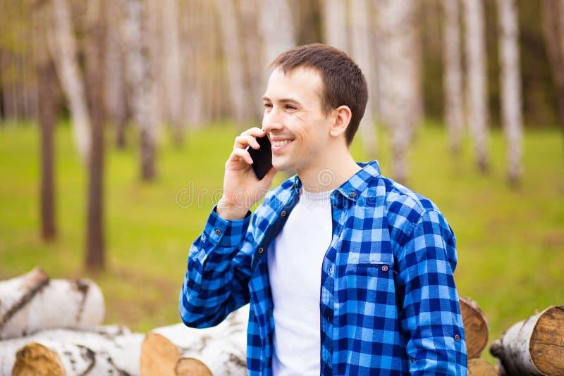 Bilden av den lyckliga unga mannen som går i stad, parkerar och talar vid telefonen royaltyfri bild