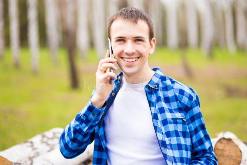 Bilden av den lyckliga unga mannen som g?r i stad, parkerar och talar vid telefonen royaltyfri foto
