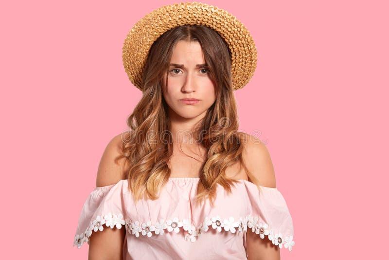 Bilden av den missnöjda unga kvinnan med ledset uttryck, gillar inte något, bär den headgeear och trendiga blusen som över isoler arkivbild