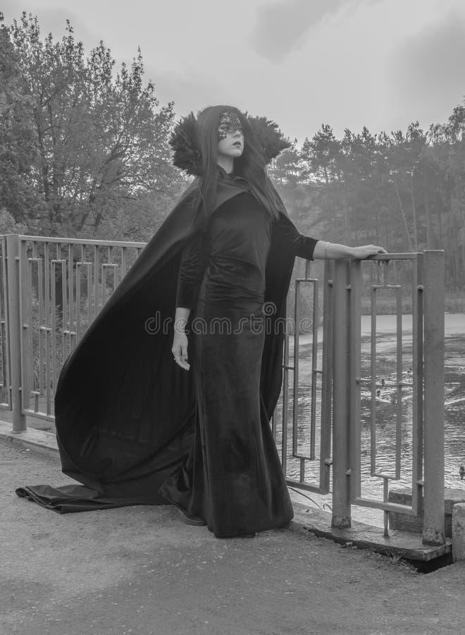 Bilden av den nätta flickan för allhelgonaafton i en klänning och en maskering som går över bron i svartvitt royaltyfri bild