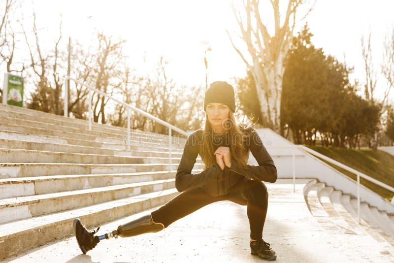 Bilden av den rörelsehindrade rinnande flickan i sportswear som gör sitter ups och arkivbild