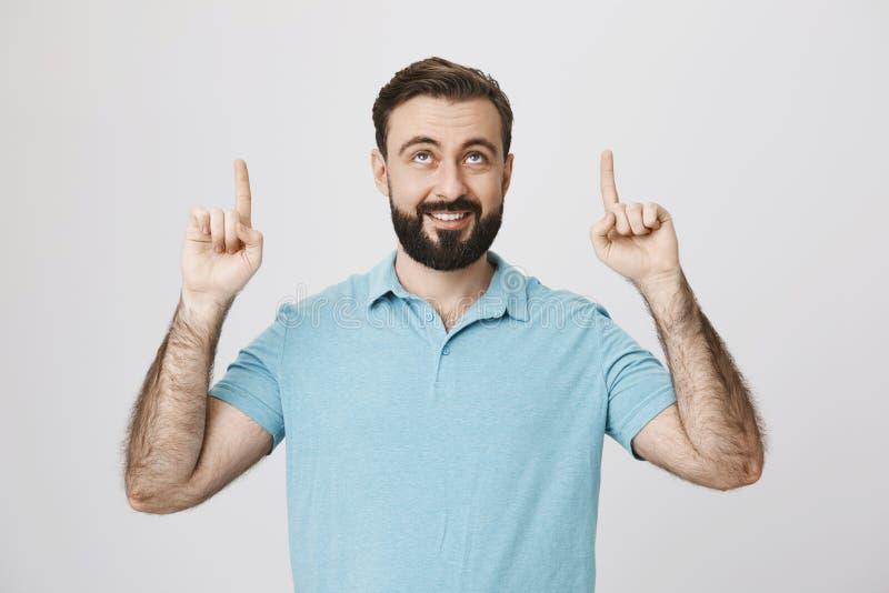 Bilden av den stiliga mitt åldrades mannen som ler, och peka hans fingrar upp i ett lyckligt posera Är så här hur segern känner s royaltyfria foton