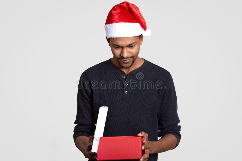 Bilden av den stiliga unga mannen med mörk hud, ser förvånansvärt på gåvaasken, bär den Santa Claus hatten, det iklädda förklädet royaltyfri bild