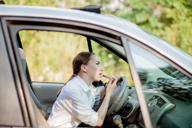 Bilden av den unga affärskvinnan talar vid telefonen och göramakeup, medan köra en bil i trafikstockningen arkivbilder