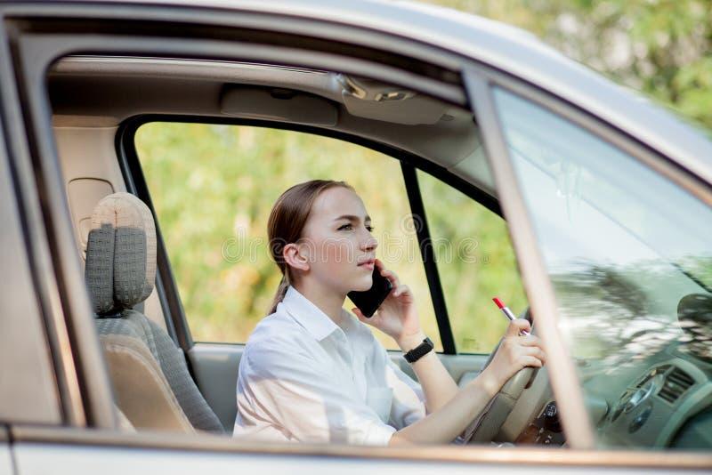 Bilden av den unga affärskvinnan talar vid telefonen och göramakeup, medan köra en bil i trafikstockningen royaltyfri bild