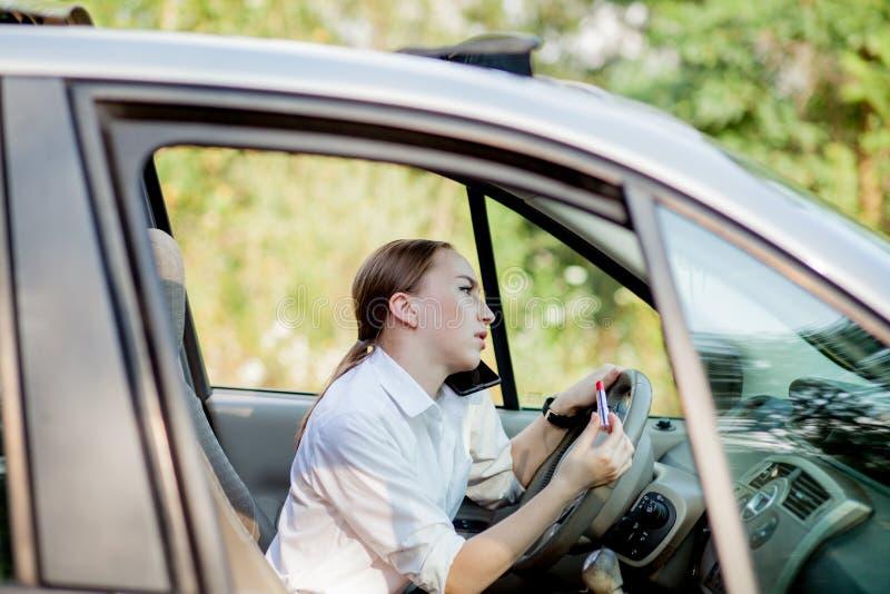 Bilden av den unga affärskvinnan talar vid telefonen och göramakeup, medan köra en bil i trafikstockningen royaltyfria foton
