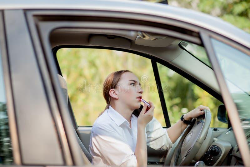 Bilden av den unga affärskvinnan talar vid telefonen och göramakeup, medan köra en bil i trafikstockningen royaltyfri fotografi