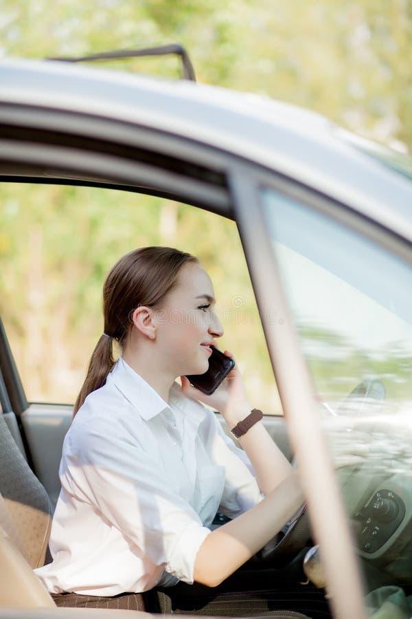 Bilden av den unga affärskvinnan talar vid telefonen och göramakeup, medan köra en bil i trafikstockningen royaltyfri foto