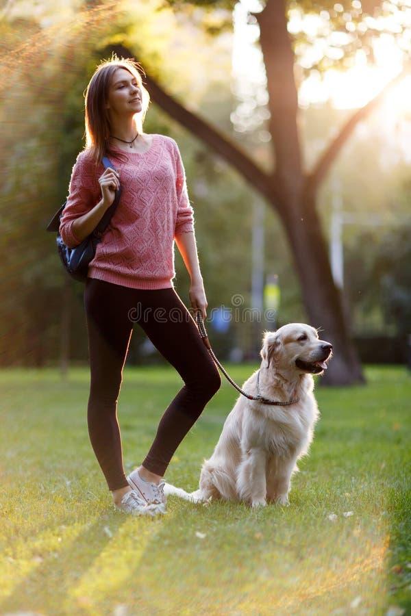 Bilden av den unga brunetten går på med hunden i sommar parkerar royaltyfri foto
