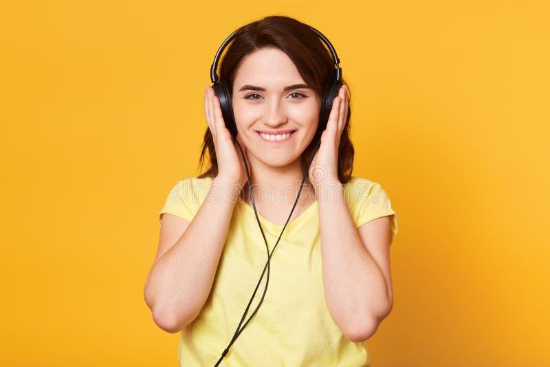 Bilden av den unga lyckliga kvinnan med hörlurar som lyssnar till musik som isoleras över den gula bakgrundsväggen och att vara i royaltyfri foto