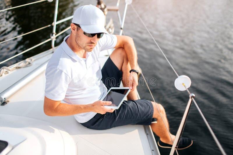 Bilden av den unga mannen sitter på kanten av yachtbrädet och hållminnestavlan Det har den mörka skärmen Mannen bär solglasögon o arkivbilder