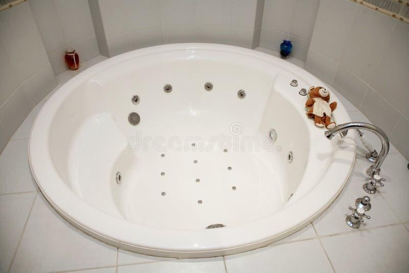 Bilden av det runda vita badrummet för varma bad dekorerade med ljusa tegelplattor arkivbild