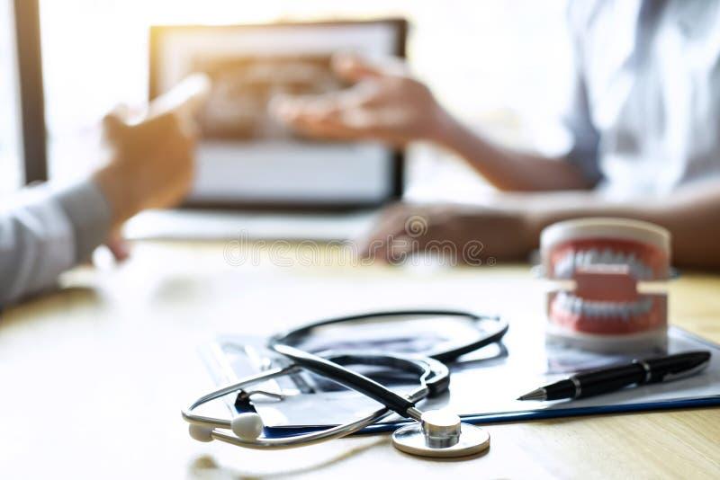 Bilden av doktorn eller tandläkaren som framlägger med tandröntgenstrålefilmen, rekommenderar tålmodig i behandlingen av tand- oc royaltyfri foto