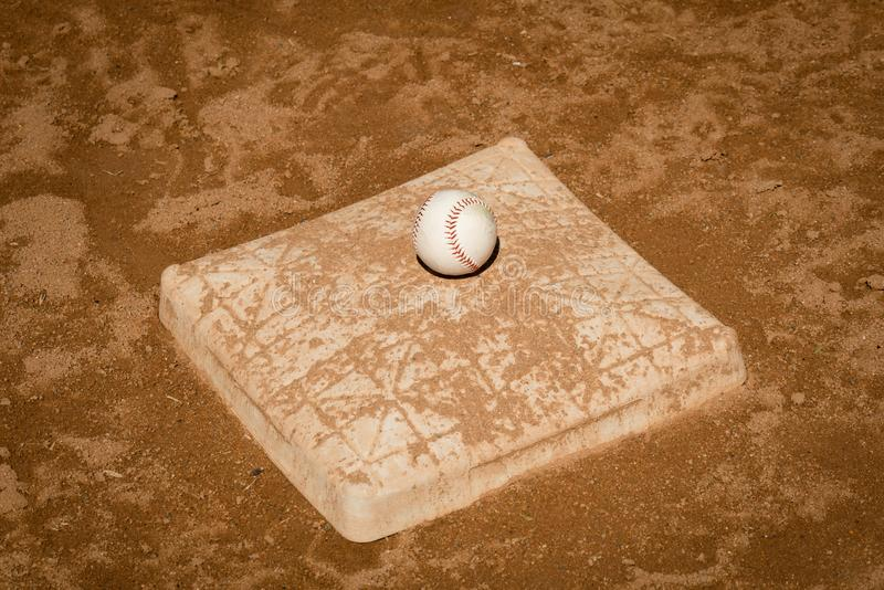 Bilden av en baseball på en smuts täckte tredje basen royaltyfri foto