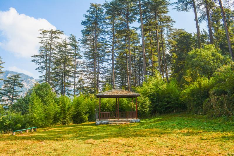 Bilden av en bergstopp med grönt gräs, högväxta träd i bakgrund, blå himmel, en träbänk och en liten koja formade bildande royaltyfria bilder