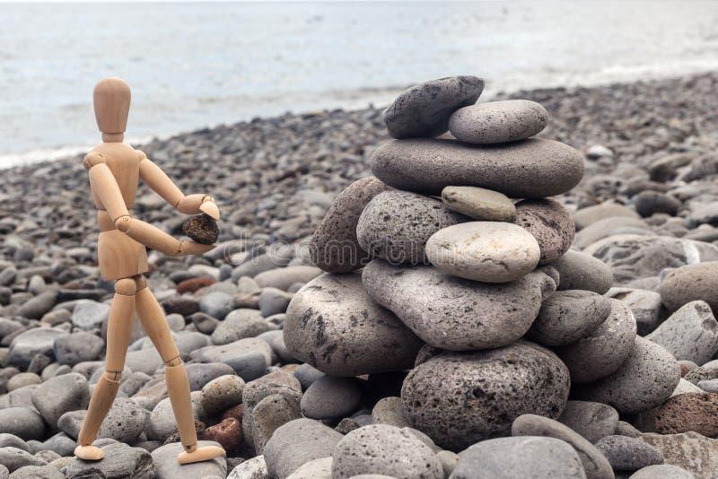 Bilden av en träman bygger en pyramid av stenar på stranden arkivfoton