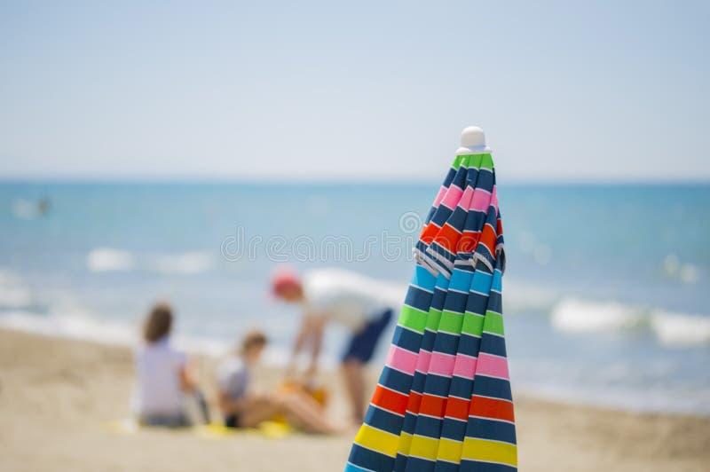 Bilden av ett flerfärgat solparaply stängde sig med folk royaltyfri fotografi