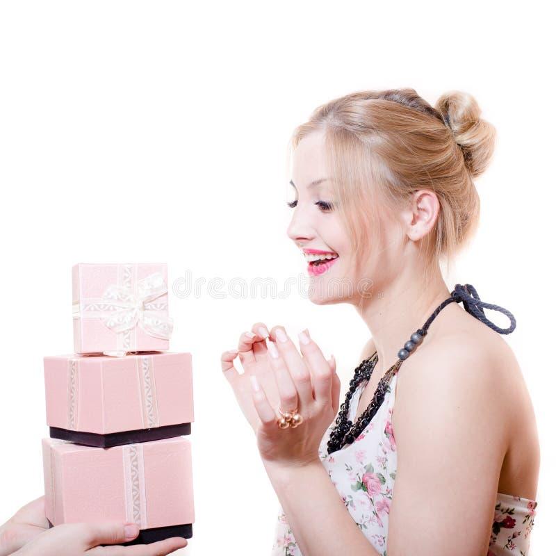 Bilden av hälerigåvor eller gåvor förvånade den attraktiva blonda unga eleganta damen som har roligt lyckligt le att isoleras royaltyfri fotografi