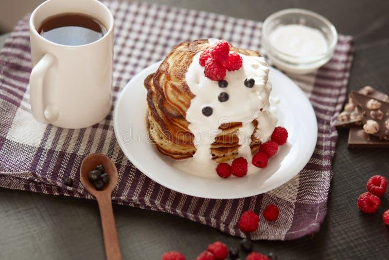 Bilden av hemmet gjorde pannkakor med gräddfil på den vita plattan som dekorerades med bär, nya blåbär och hallon, kopp te arkivfoto