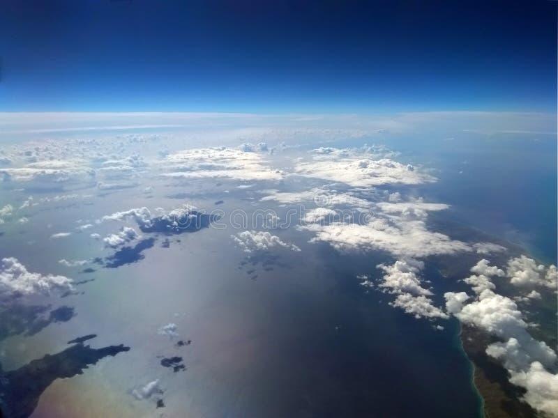 Bilden av jorden med blå himmel och vit fördunklar över havet med solen reflekterad på vattnet och de lilla öarna arkivfoton